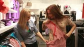 consumismo : Two girlfriends enjoying shopping trying various garments and having fun
