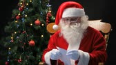 natal : Santa Claus sitting in the chair and reading Christmas letters sent by children Vídeos