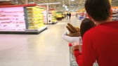 corredor : Cheerful couple having fun in supermarket riding a cart