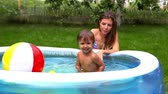 inflável : Adorable little girl spending time outdoors in an inflatable pool, her mom being with her