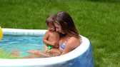 inflável : Family of two having fun in an inflatable pool settled on the lawn