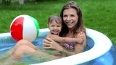 piscina : Mom and daughter sitting in a pool and enjoying spending time together