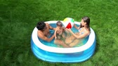 inflável : Family of three sitting in an inflatable pool in the backyard and enjoying their summer leisure