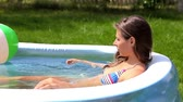 inflável : Smiling young woman spending her peaceful summer outdoors in an inflatable pool