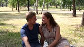 amor : Tilt down of a charming couple sitting on the blanket in park and enjoying themselves