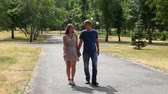 amor : Lovely young couple walking together in the park holding hands