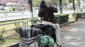 pobreza : Homeless man driving the cart with his belongings along the city streets Vídeos