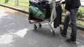 cart : Homeless guy with a limp pushing a shopping cart full of dirty clothes Stock Footage