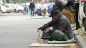 pobreza : Beggar sitting in the street waiting for coins