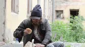 bêbado : Homeless man sitting on a porch of a derelict house having a booze and a snack