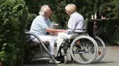 querido : Retired couple spending time outdoors, wife sitting in a wheelchair