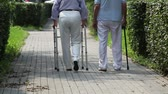cana : Elderly couple taking steps together with a help of a walker and a cane