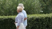 querido : Elderly couple strolling arm-in-arm along the green hedge, man using a cane  Stock Footage
