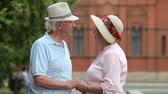 sincero : Tilt up of charming elderly people holding hands and expressing their affection