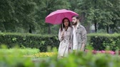 guarda chuva : Young couple under umbrella walking among flowers in the park
