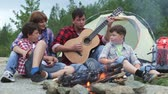 fogo : Camping family gathering around dad who is playing the guitar and singing