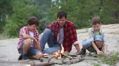 lenha : Father and sons getting warm at the camp fire