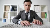 entrada : Serious office worker looking at the viewer and typing   Stock Footage