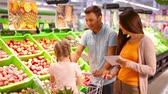 supermarket : Family of three passing fruit section in the mall taking some with them