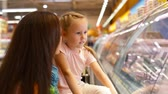 refrigerator : Mother and daughter being by the refrigerated case choosing what to buy