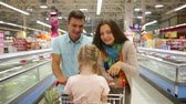 empurrando : Smiling parents pushing a shopping trolley with their daughter sitting inside