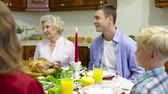 saying : Family gathered at festive dinner saying a prayer before eating Stock Footage
