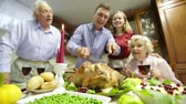 parcela : Young man cutting roasted turkey in pieces to share with his family