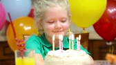 wish : Cute little girl thinking over her birthday wish and blowing out the candles