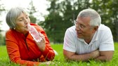 sedento : Elderly couple having a rest after an outdoor workout sharing a bottle of water