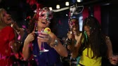 discoteca : Girls in masks partying when their friend fires a petard with confetti Stock Footage