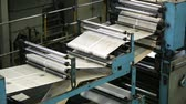 automático : Black-and-white newspaper sheets moving through rollers along the production line Stock Footage