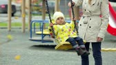 развлекательный : Mother pushing the swings entertaining her little child