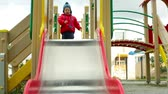 jardim de infância : Active lad sliding down the chute on the playground