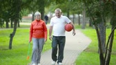 Active seniors wearing sportswear walking along the park lane