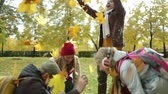 outdoors : Happy family of four playing with leaves in the park in autumn