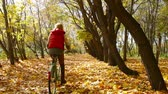 dráha : Red-haired guy cycling down the park lane covered with fallen leaves