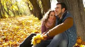 leaf : Flirty couple cuddling by the tree in the autumn park Stock Footage