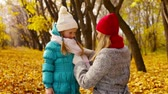 scarf : Caring mom putting a knitted scarf on her little daughter to keep her warm