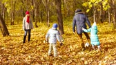 carinho : Dad kicking the ball together with his kids in the autumn forest