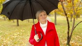 guarda chuva : Elegant elderly lady with a candid smile enjoying a rainy day