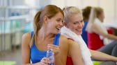 sedento : Girls being tired after workout sharing water to avoid dehydration