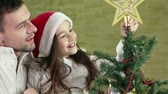 decor : Lovely girl putting a shining star at the top of the Christmas tree with the help of her dad