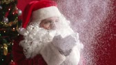 seasonal : Slow-motion of Santa Claus blowing snow and looking at camera with a positive expression
