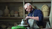 mestre : Experienced master doing a clay vase on a pottery wheel
