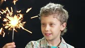magia : Preteen boy being excited with a bright sparkler in his hand, shifting focus
