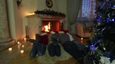 advent decorations : Family of four lying in front of the fireplace and enjoying their comfy Christmas at home