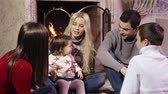 lareira : Slow-motion of a cheerful family sitting by the fire and giving each other a high five
