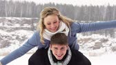 nevando : Couple enjoying their winter weekend together, guy holding his girlfriend piggyback