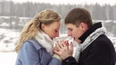 снег : Caring guy warming the hands of his girlfriend