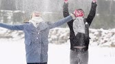 снегопад : Slow-motion of ecstatic young people throwing snow up in the air and hugging  Стоковые видеозаписи